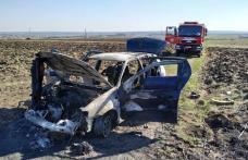 Mașină distrusă de foc după ce șoferul a oprit să stingă un incendiu de vegetație - FOTO